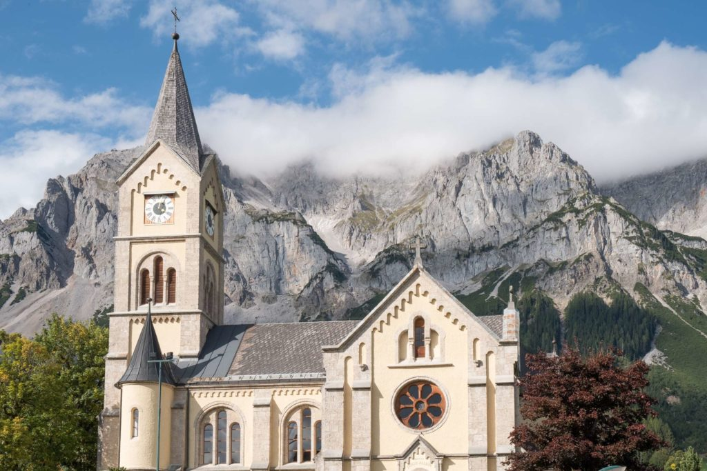 Protestant church in Ramsau am Dachstein with Dachstein mountain range towering in the back