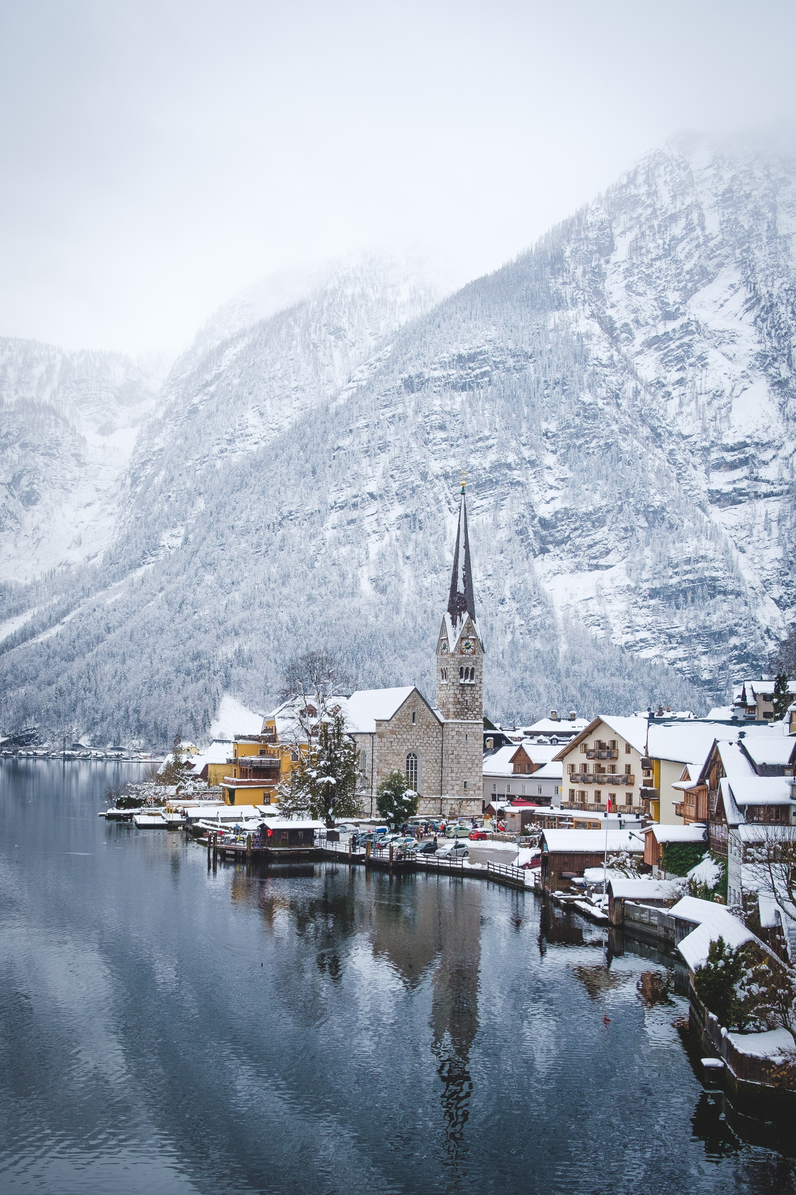Hallstatt in the snow with focus on the church at the lake front