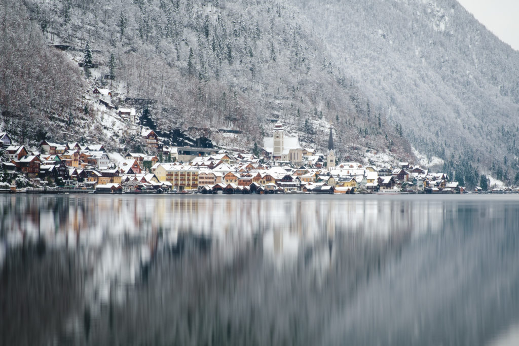 Hallstatt in the snow and its reflections on the lake