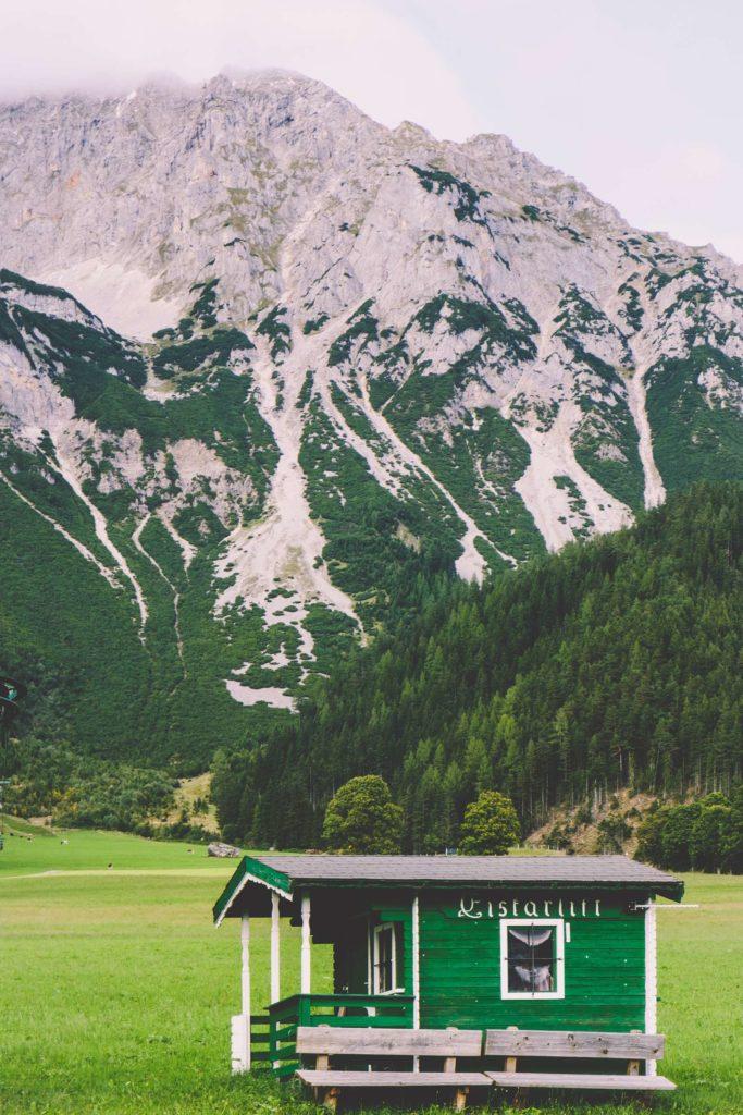 A picturesque little wooden hut in Ramsau am Dachstein in front of the Dachstein mountain range
