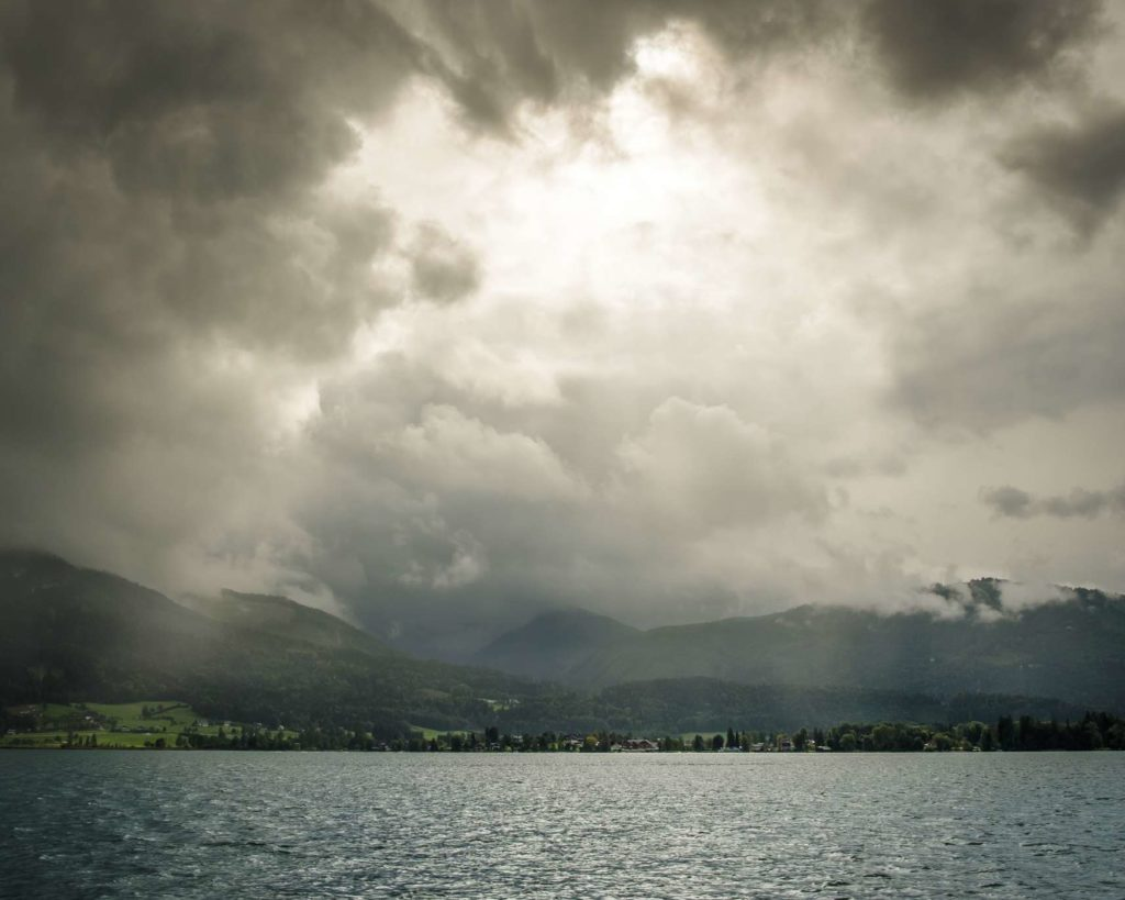 Stormy weather over Wolfgangsee with rays of sunshine protruding through the clouds