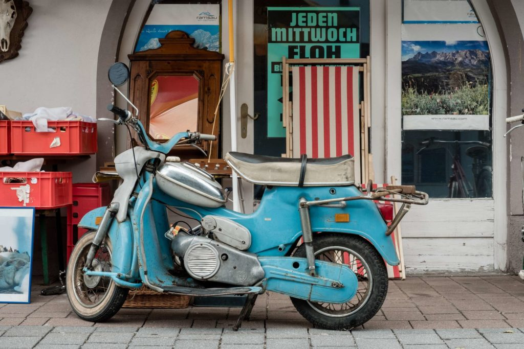 A somewhat battered blue vintage scooter in front of a secondhand store in Ramsau am Dachstein