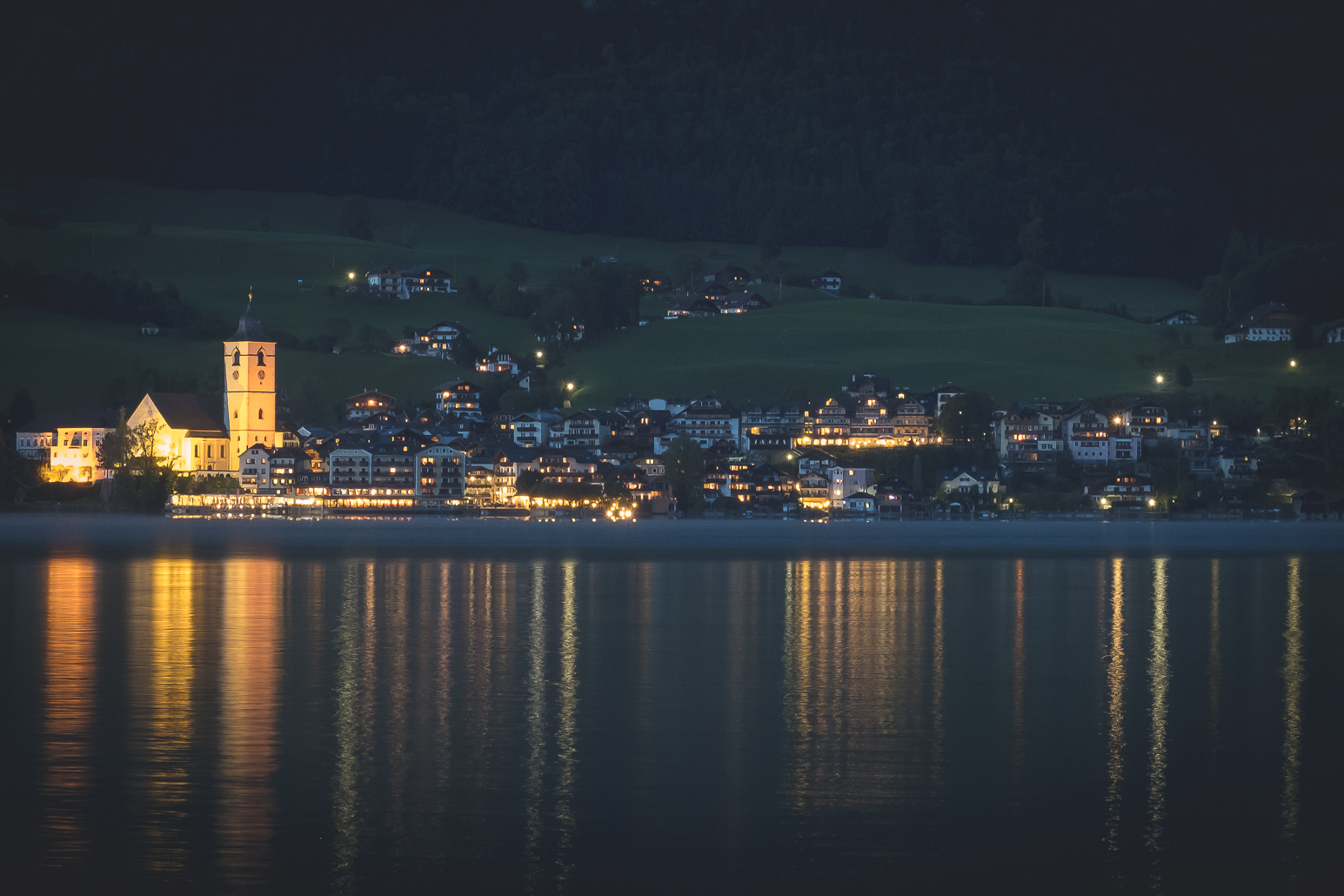 St Wolfgang at night reflecting in the lake from the opposite shore