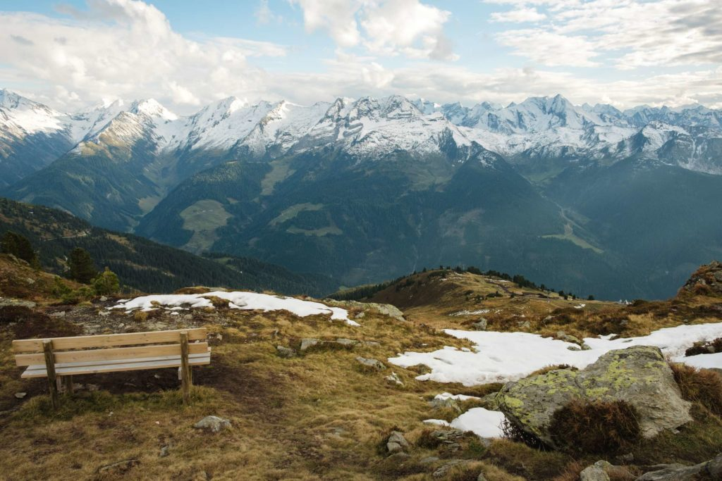 A bench at the top of Karspitze with a mountain range in the background