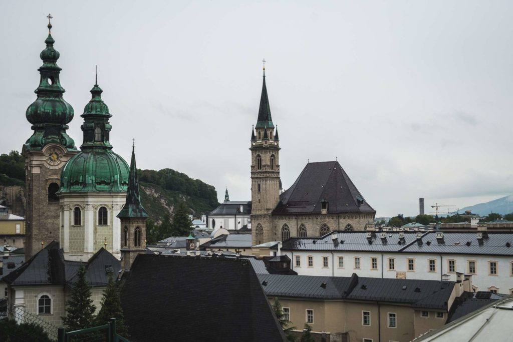 View over moody, rainy Salzburg, with church towers rising above medieval buildings