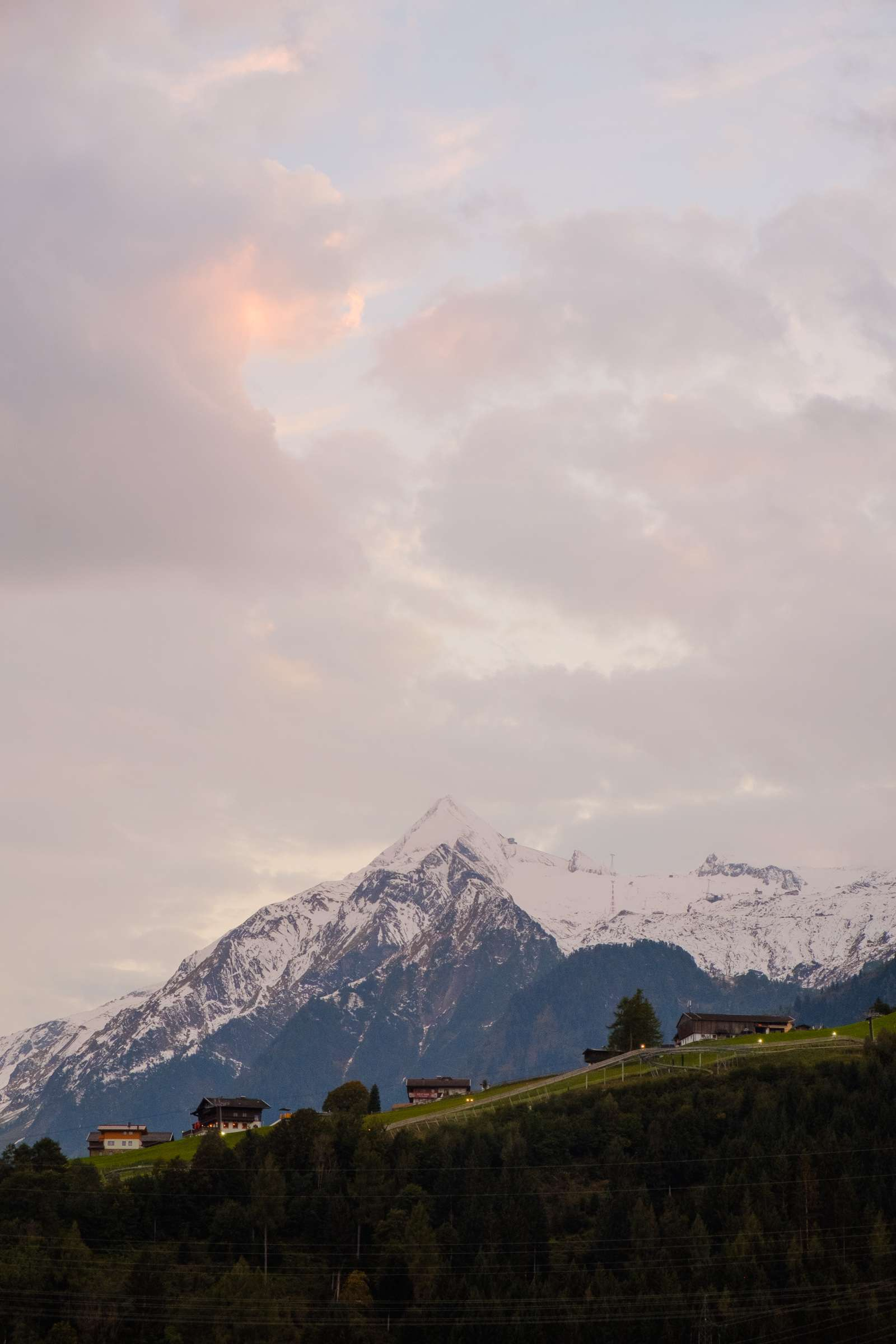 Pink fluffy sunset over Kitzsteinhorn with wooden houses in the foreground