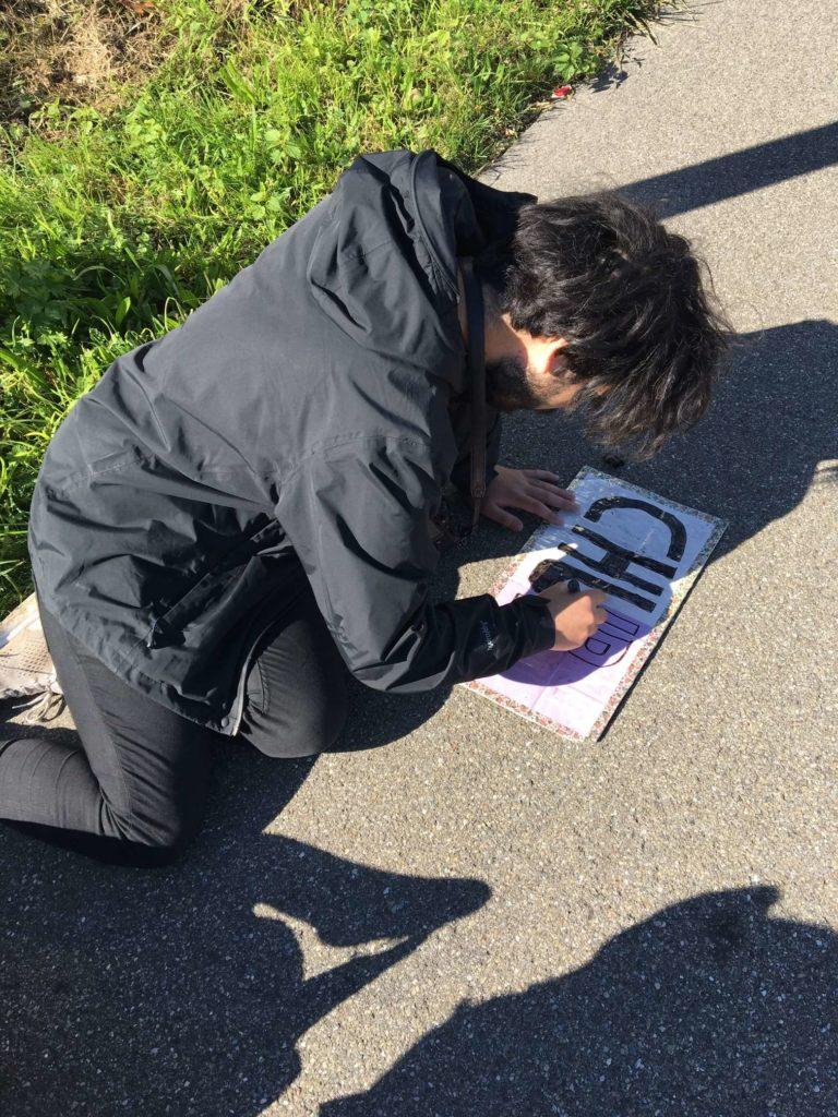 Aydin writing hitchhiking sign to Chur