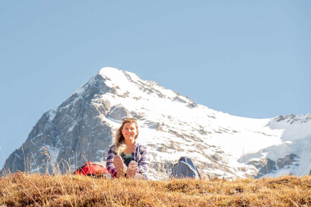 Caroline enjoying the sun below snowy peak