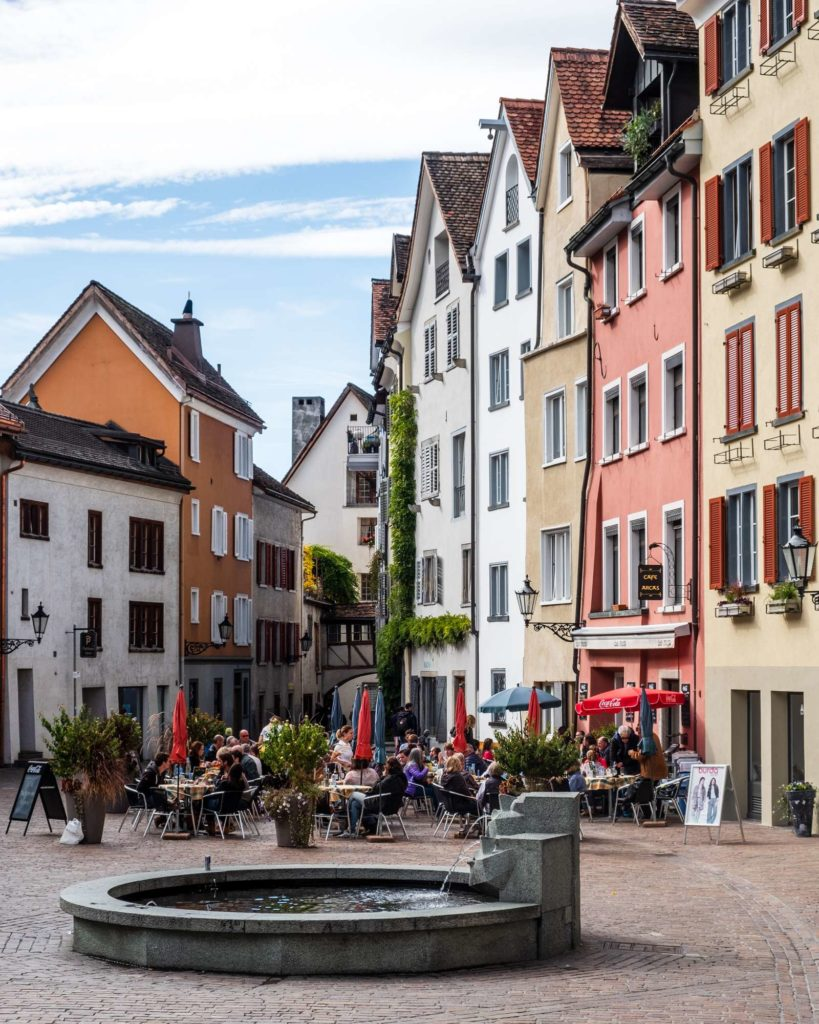 The town square of Chur with a small fountain and tall narrow medieval buildings