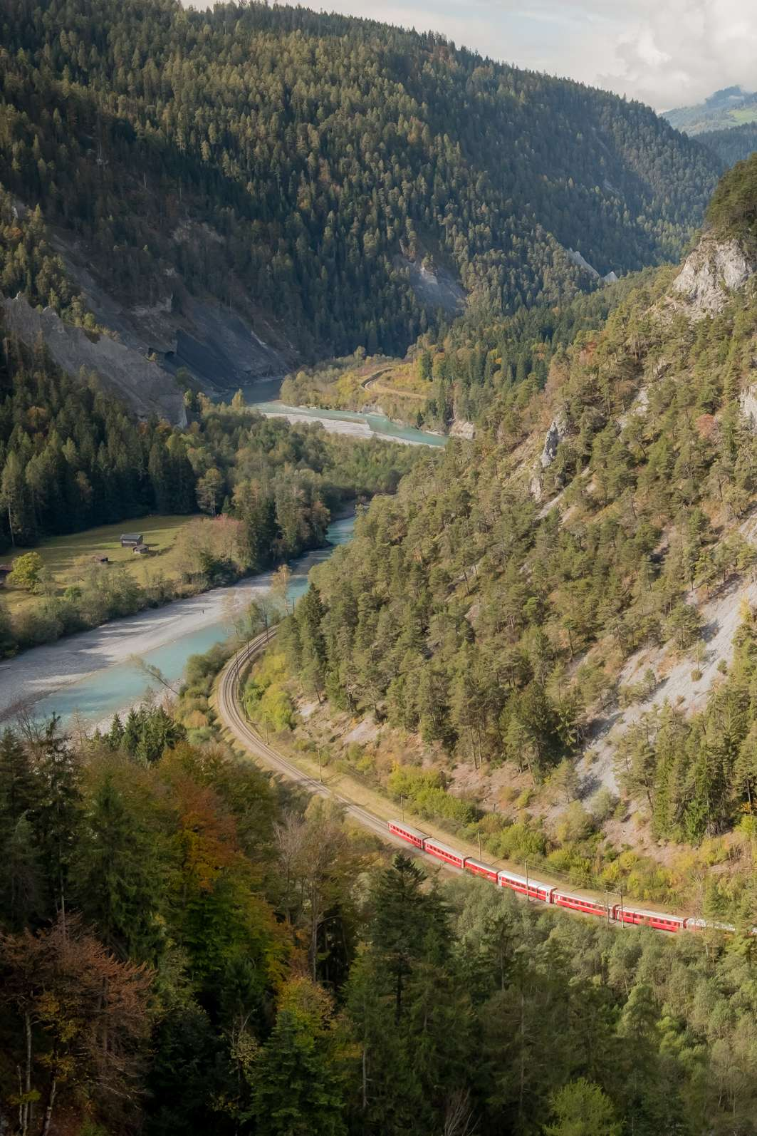 The Glacier Express train in the Grand Canyon of Switzerland, weaving through the valley next to the chalk coloured Rhine