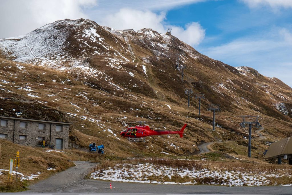 A red helicopter taking off on Oberalppass