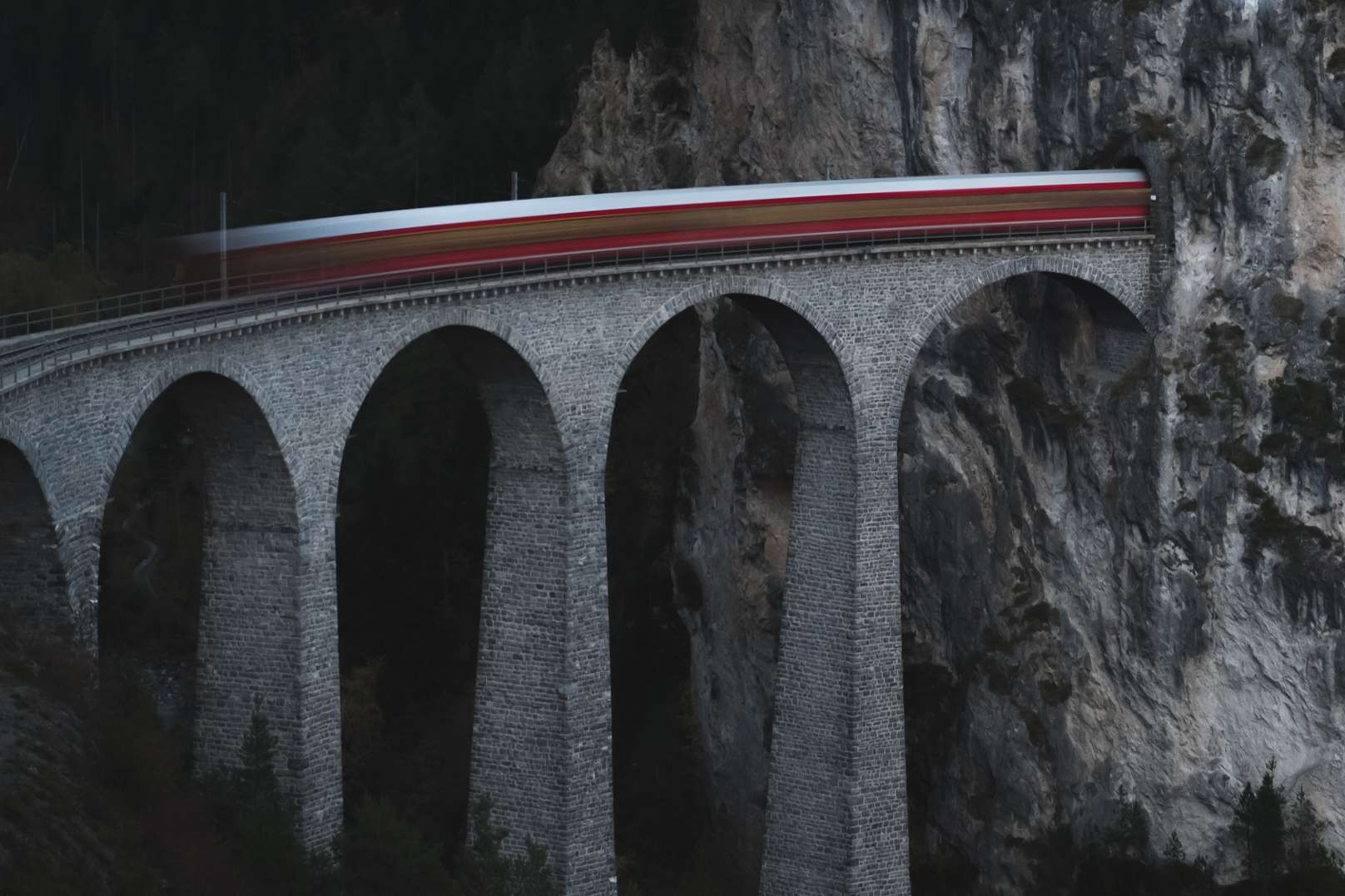 A blurred long exposure photo of a train going across the Landwasser Viaduct on the Glacier Express