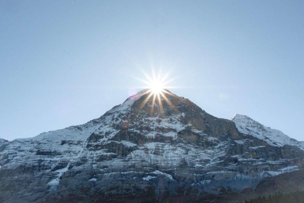 The sun peeking over the top of a mountain
