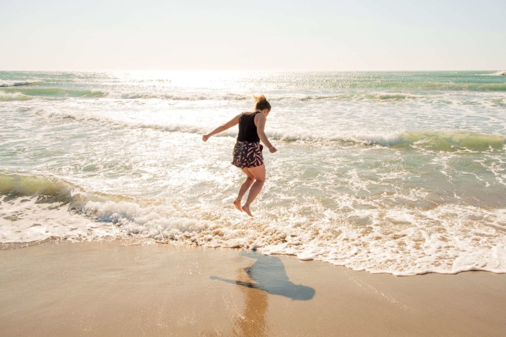 Caroline jumping in the water on the beach