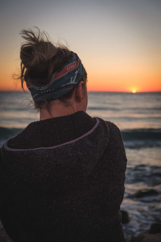 Caroline watching the sea with out of focus sunset