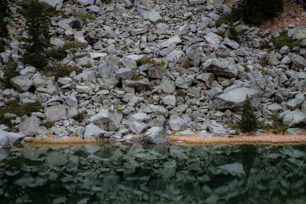Huge boulders tumbling into small lake