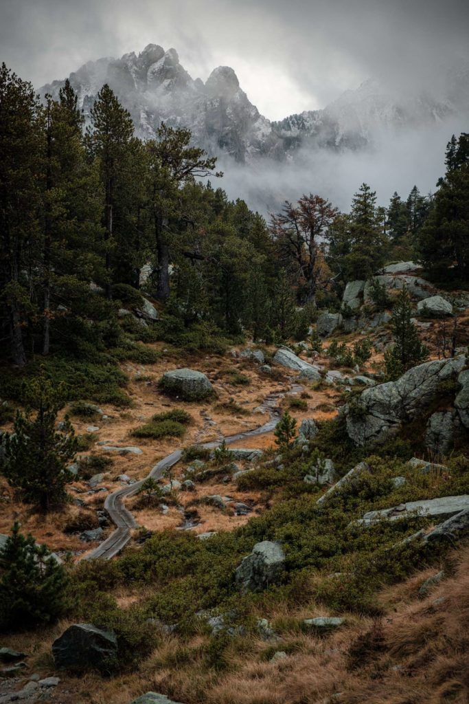 Winding path to cloud covered mountains in Aigüestortes i Estany of Saint Maurici national park