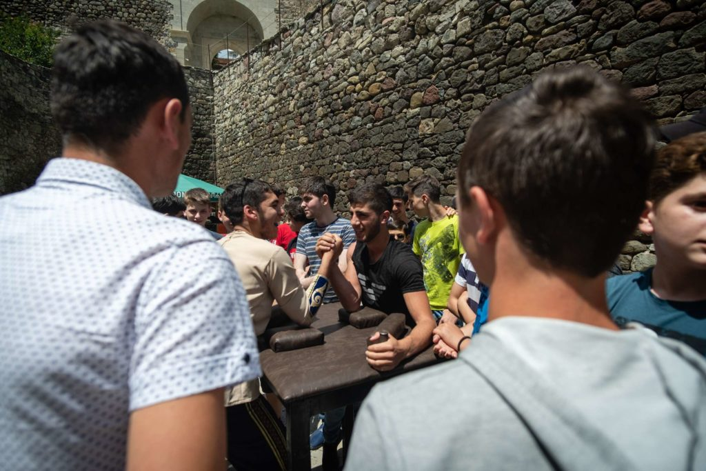 Young men doing arm-wrestling during independence day, Rabati Castle, surrounded by people cheering them on