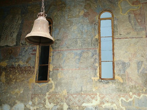 Bell in Vardzia Church of Assumption with frescoes in the back