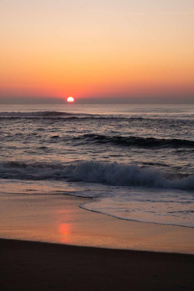 Aveiro beach sunset with sun reflecting on beach