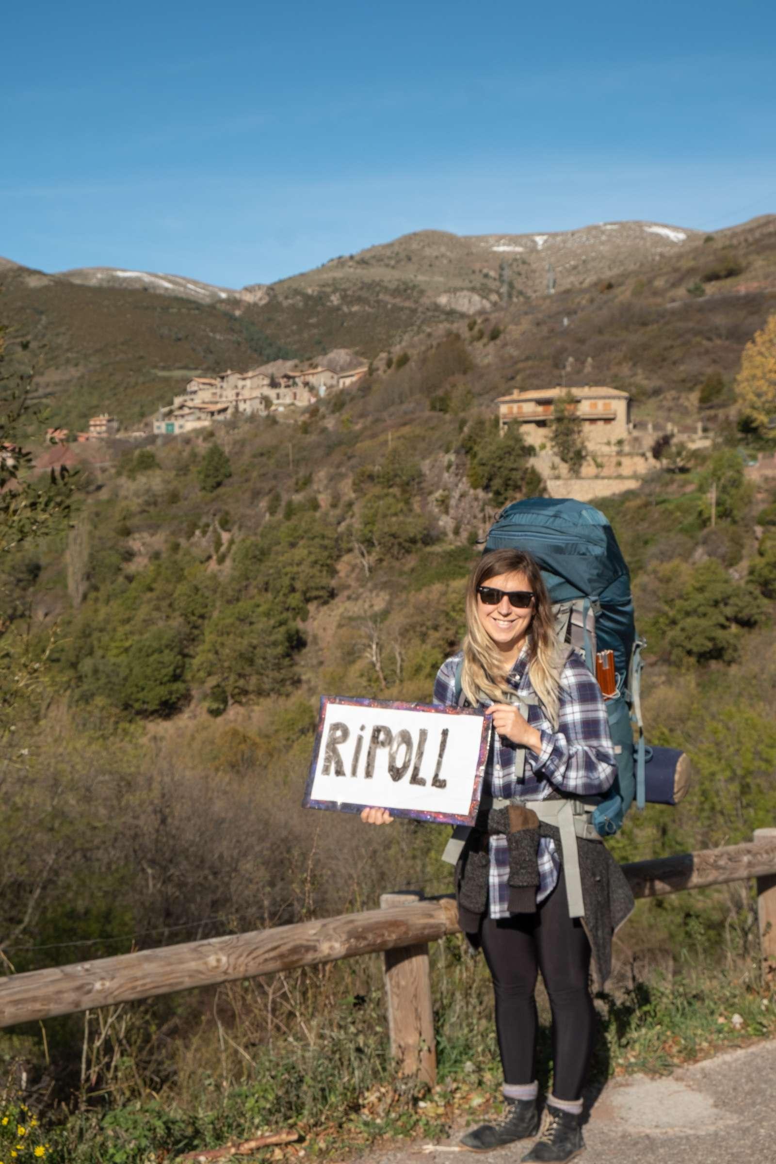 Caroline holding the hitchhiking sign on Catalonia outside of Castellar de n'Hug