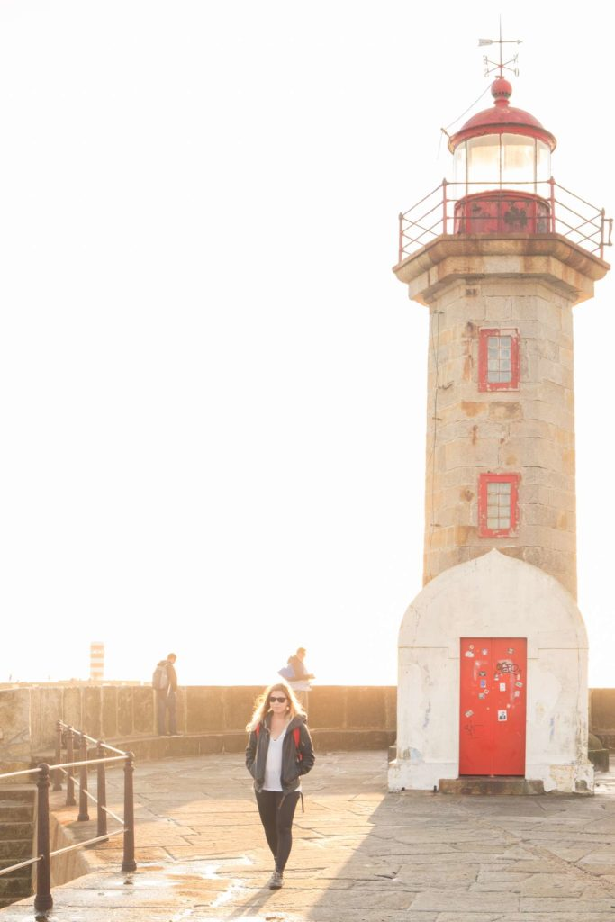 Caroline walking away from lighthouse backlit by the sun