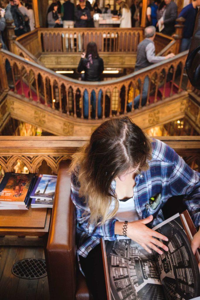 Caroline reading book in Livraria Lello