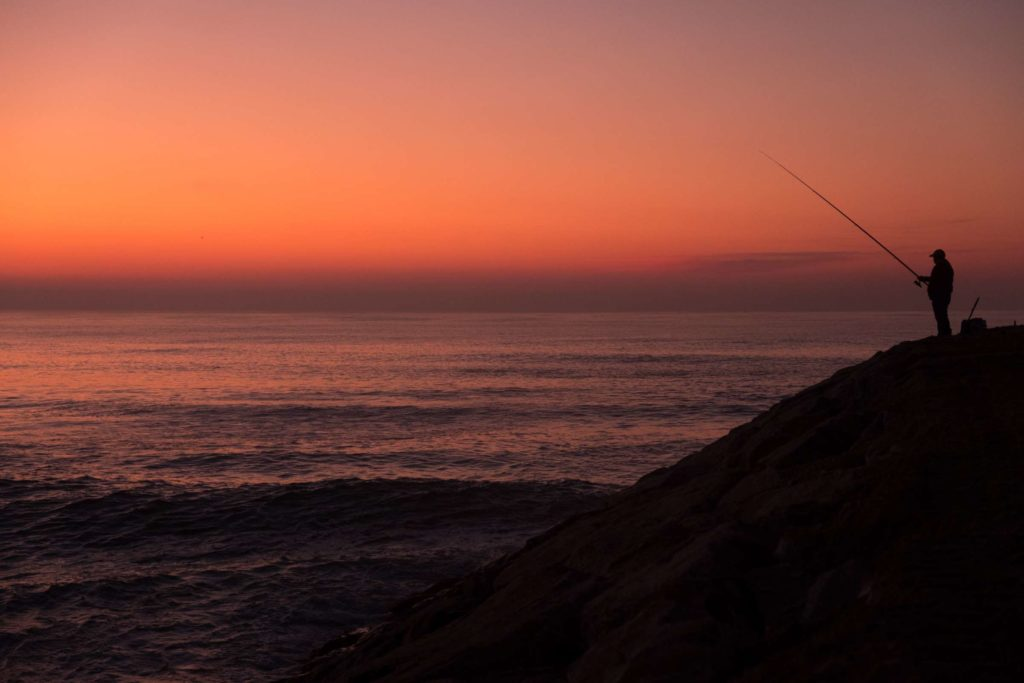 Lone fisherman in sunset at Costa Nova beach