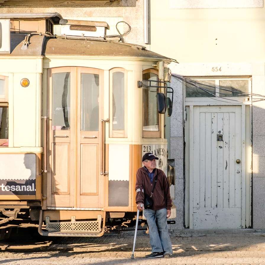 Old man leaning against a tram in Porto