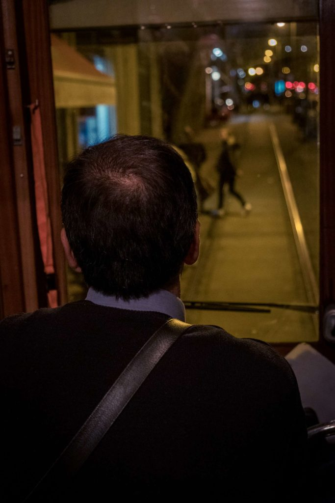 Tram driver with people on the street moving out the way