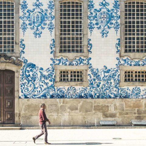 Man walking past side of Igreja do Carmo