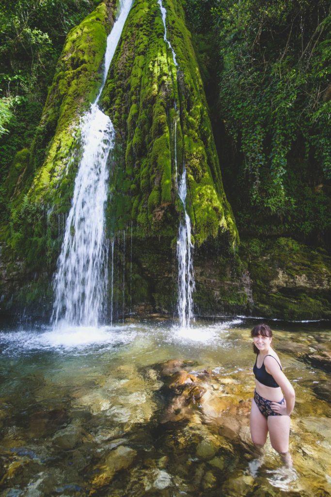 Caroline standing in front of Kaghu waterfall (კაღუს ჩანჩქერი) on Abasha river