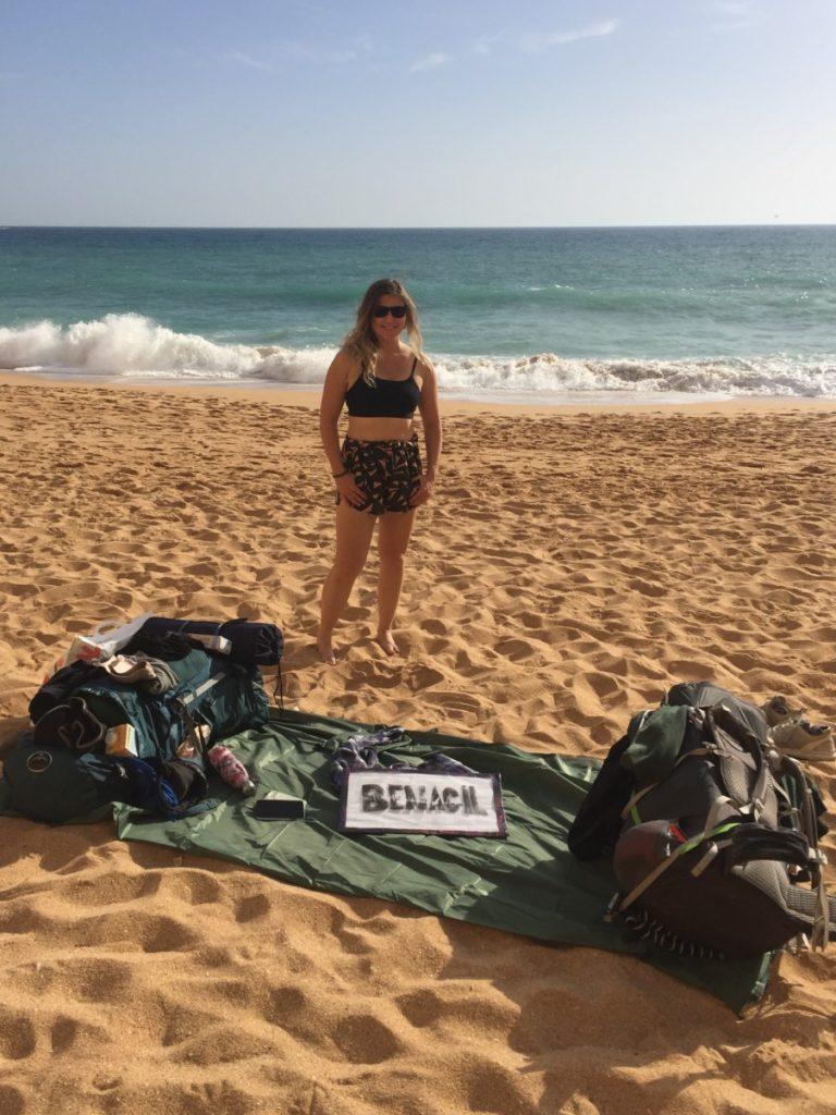 Caroline standing proud on Benagil beach with hitchhiking sign and rucksacks