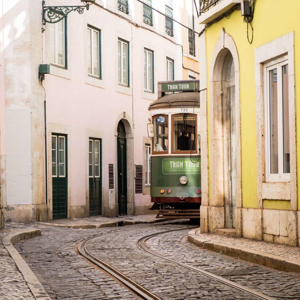 Cute green tram around a tight corner in Alfama, Lisbon
