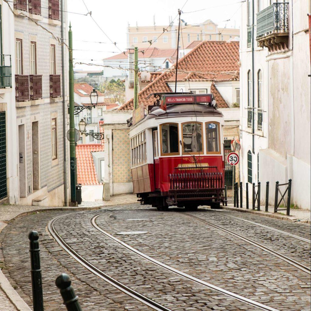 Cute red tram on cobbled street in Alfama, Lisbon
