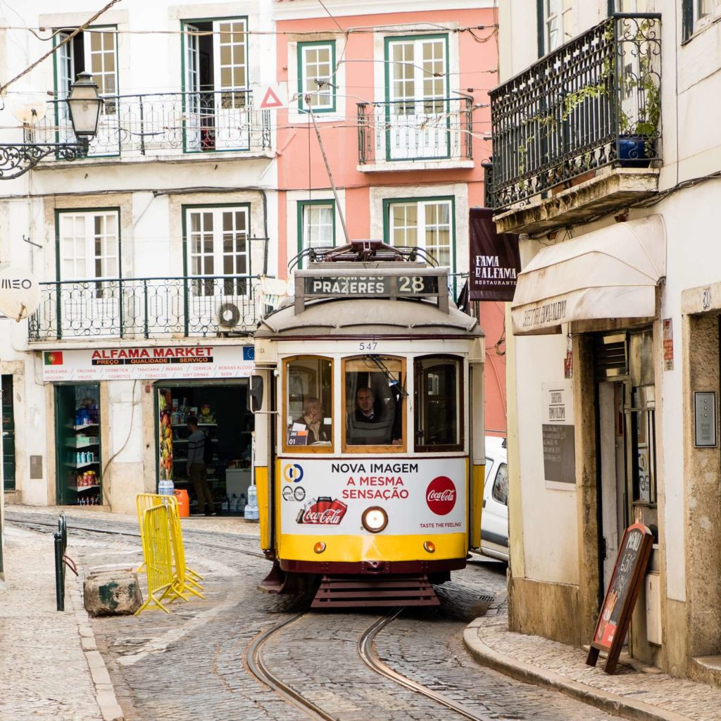 Cute yellow tram in a tight spot in Alfama, Lisbon