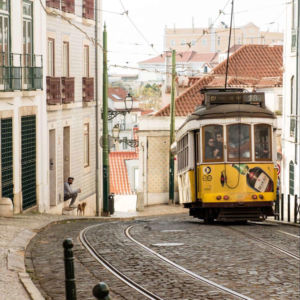 Cute yellow tram on cobbled street in Alfama, Lisbon