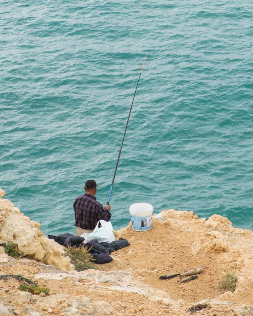 Fisherman fishing on the cliffs of the Algarve