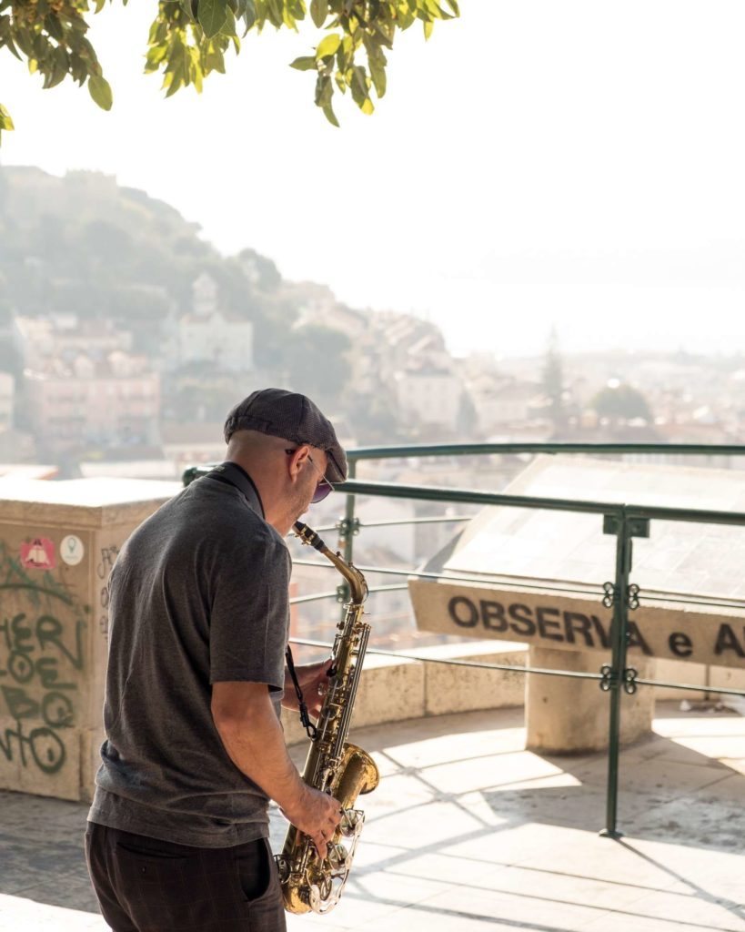 Man playing the Sax at Miradouro da Graca viewpoint