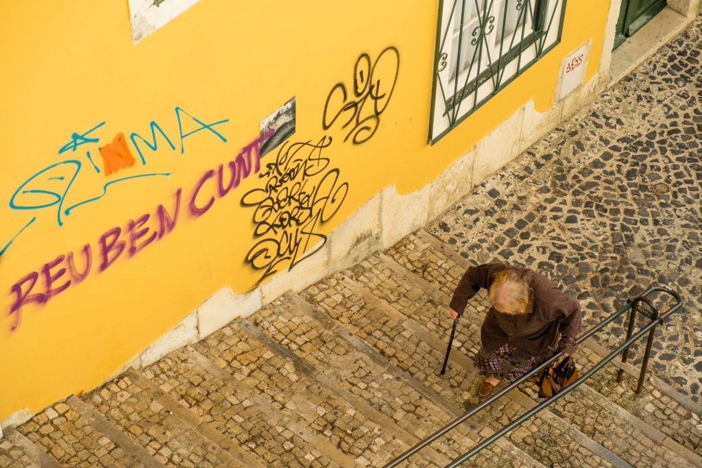 Old lady climbing cobbled staircase with graffiti on walls
