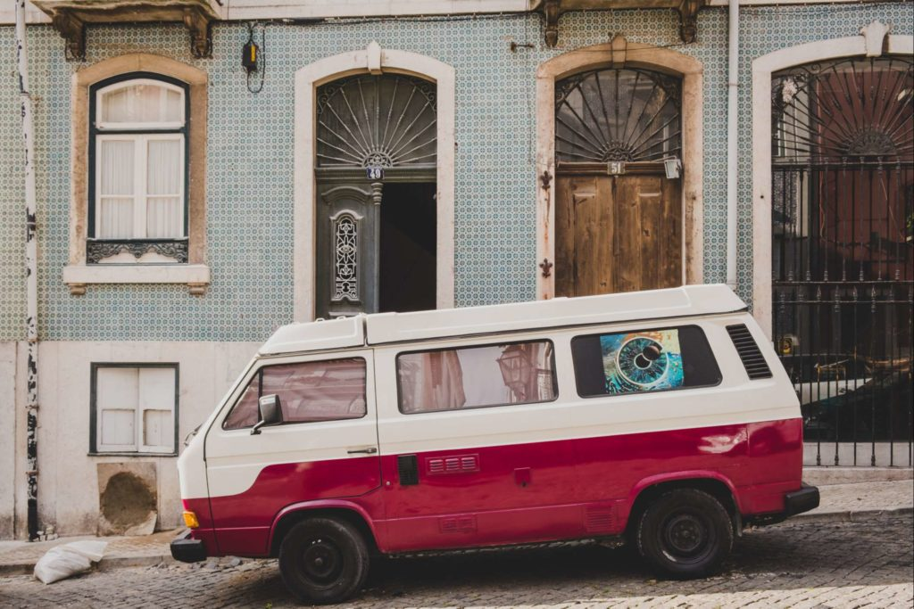 Red and white van in front of pretty house in Lisbon
