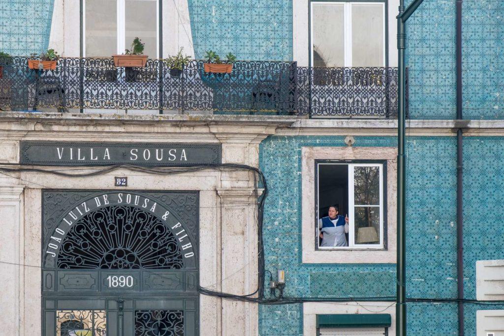 Woman smoking in window of Villa Sousa, Lisbon