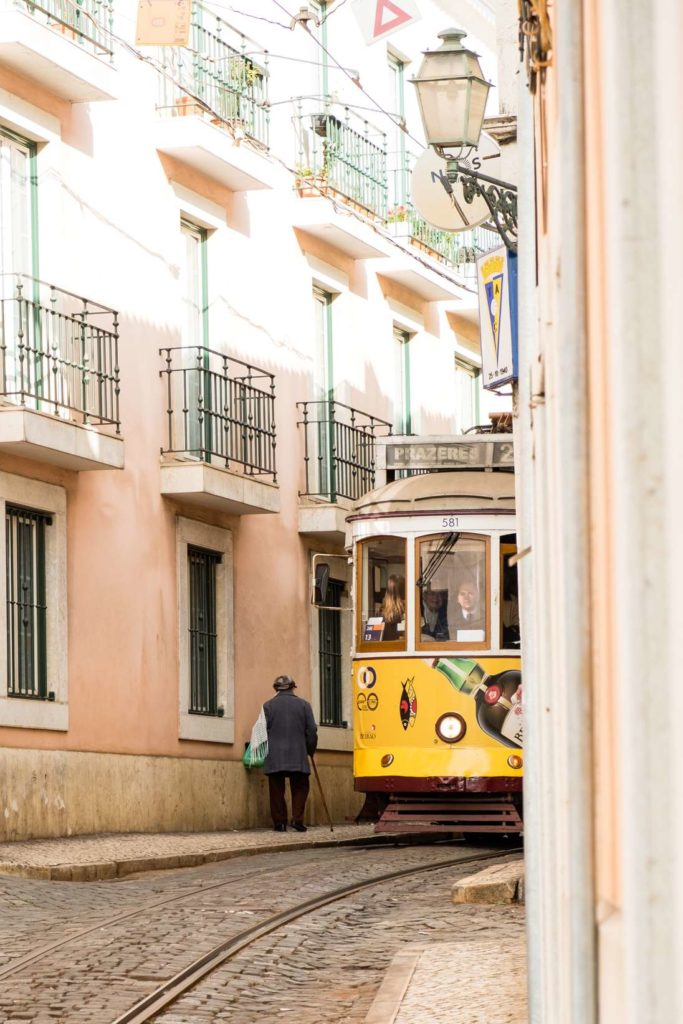 Yellow tram squeezing past old man in narrow cobbled street